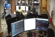 An office with people sat behind three monitors