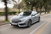 Front three-quarter view of the 2018 Honda Civic saloon driving on a tree-lined street