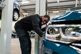 Volkswagen technician at work in VW dealership workshop