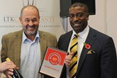 Robin Luscombe, managing director, Luscombe Motors, left, accepts the AM  Best UK Dealerships to Work For  award from LTK Consultants'  managing director, Andrew Landell