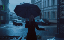 Woman standing under an umbrella in the rain