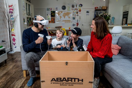 A family engaging with the Abarth 595 home test drive VR experience