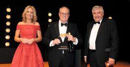 NFDA chairman David Newman (centre) collects the award on behalf of Arnold Clark Automobiles from awards judge, Professor Jim Saker of Loughborough University