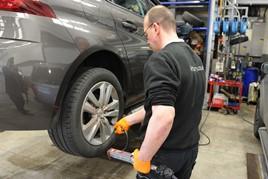A technician works on car in workshop