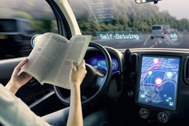 A passenger in an autonomous car reads a book while travelling