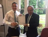 TrustFord's chairman and chief executive Stuart Foulds presents finance director Stuart Mustoe with his 20 years' service certificate.