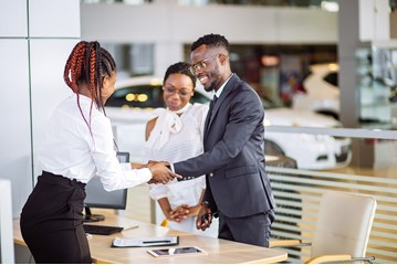 A car sale is completed with a handshake
