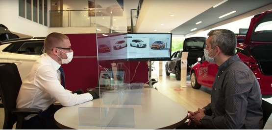 Wearing masks, a car salesman presents a new Vauxhall to a car buyer