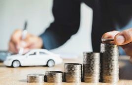 Men are putting coin and saint documents about cars with some coins calculator and car toy on desk.