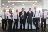 Craig Christopher receives champagne from his Robins & Day colleagues to celebrate 30 years' service