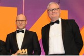 Darren Edwards, chief executive,  Sytner, left, collects  the award from Ian Simpson, sales  and marketing director, Premia  Solutions