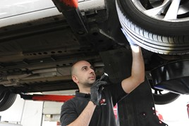 An automotive technician checking a vehicle's tyres