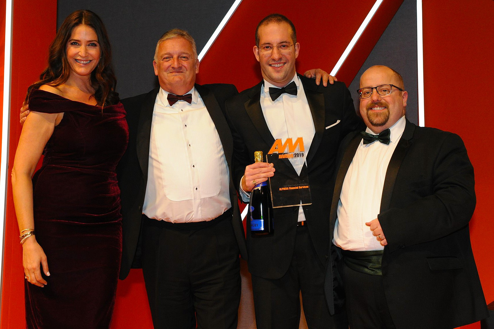 Gerry Kouris, head of marketing,  Alphera Financial Services, (second from right)  accepts the award from AM   editor Tim Rose, right and host Lisa Snowdon, left