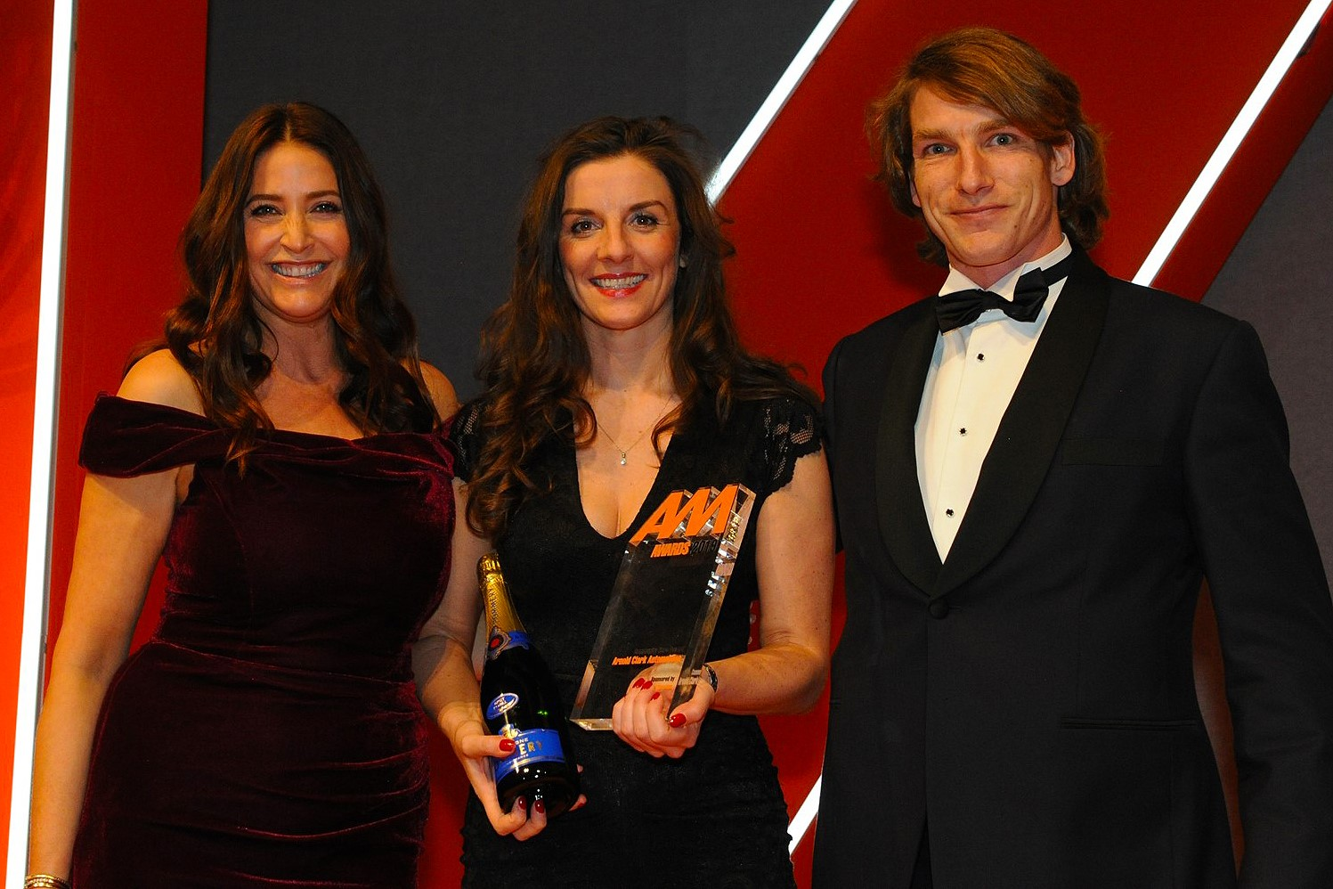 Lee-Ann Edison, head of  communications, Arnold Clark  Automobiles, accepts the award  from Freddie Hunt, Texaco  Havoline brand ambassador, right, and host Lisa Snowdon, left
