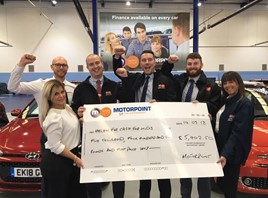 Staff from Motorpoint Sheffield present Michelle Osborne, charity fundraising executive at Cash for Kids, with a cheque following their drive-in cinema event