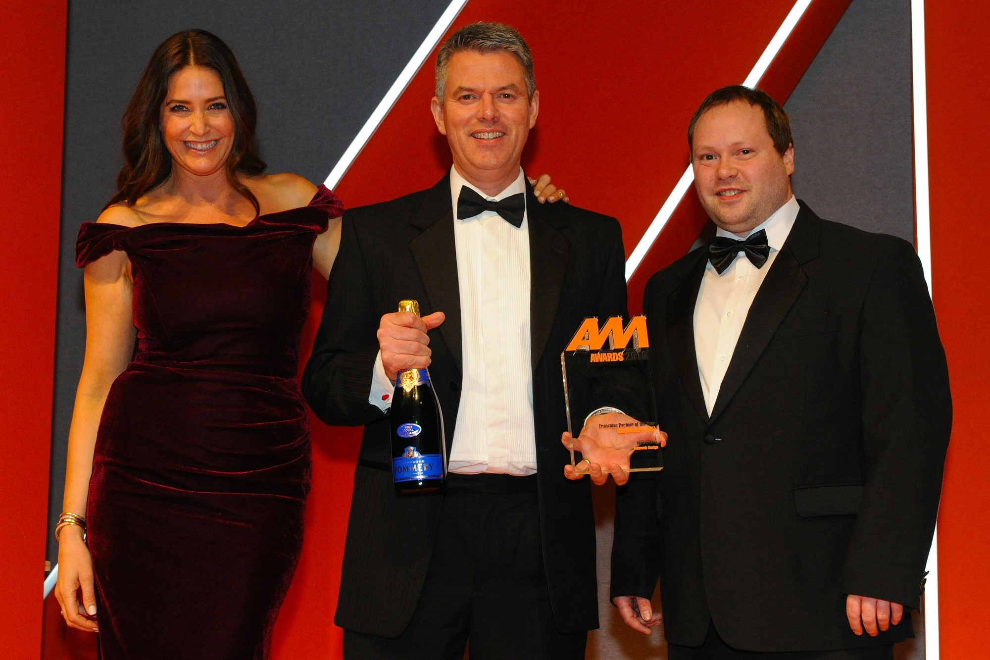 Paul Philpott, president and chief executive, Kia  Motors (UK), accepts the award from Martin Dew,  digital solutions director, Autoweb Design, right and host Lisa Snowdon, left