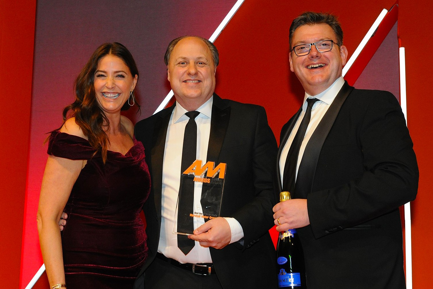 Philip J Deacon, head of marketing, Marshall Motor  Group, accepts the award from Jeremy Evans,  managing director, Marketing Delivery, right