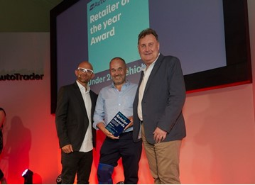 Robin Luscombe, managing director of Luscombe Motors (centre) collects his Retailer of the Year award at the Auto Trader Retail Awards 2018