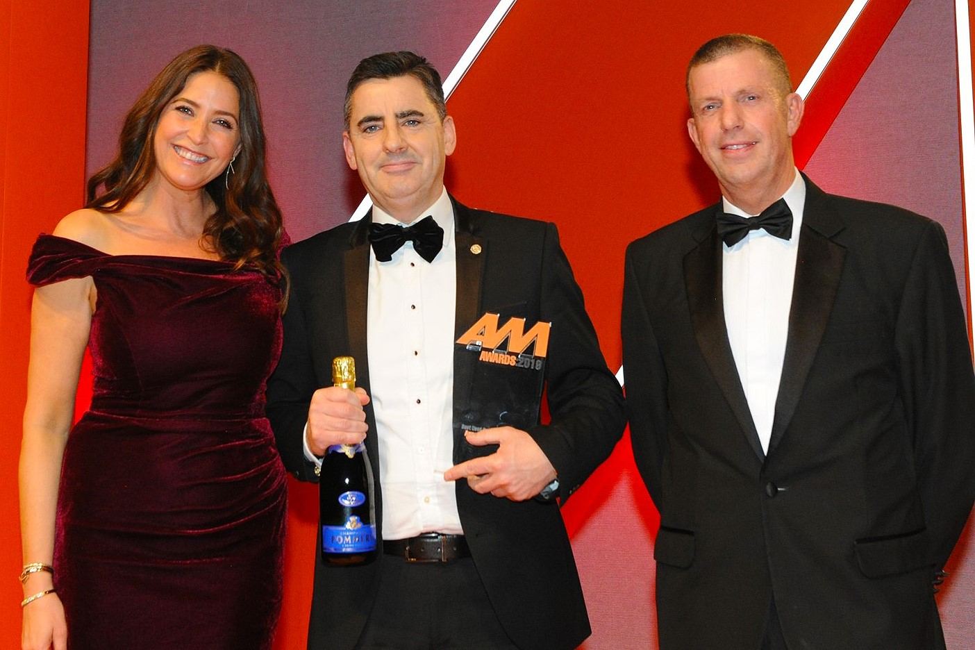 Russell Borrie, group franchise  director, Arnold Clark Automobiles,  accepts the award from Martin Ward,  managing director, Autoclenz, right and host Lisa Snowdon, left