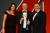 Simon Hetherington, commercial  director, Kia Motors (UK), accepts the  award from Philip Morrison, head of  corporate sales, Car Care Plan, right, and host Lisa Snowdon, left