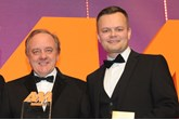 Stuart Foulds, chairman and  chief executive, TrustFord, collects the award from  Marc Robinson, sales director,  Motors.co.uk, right