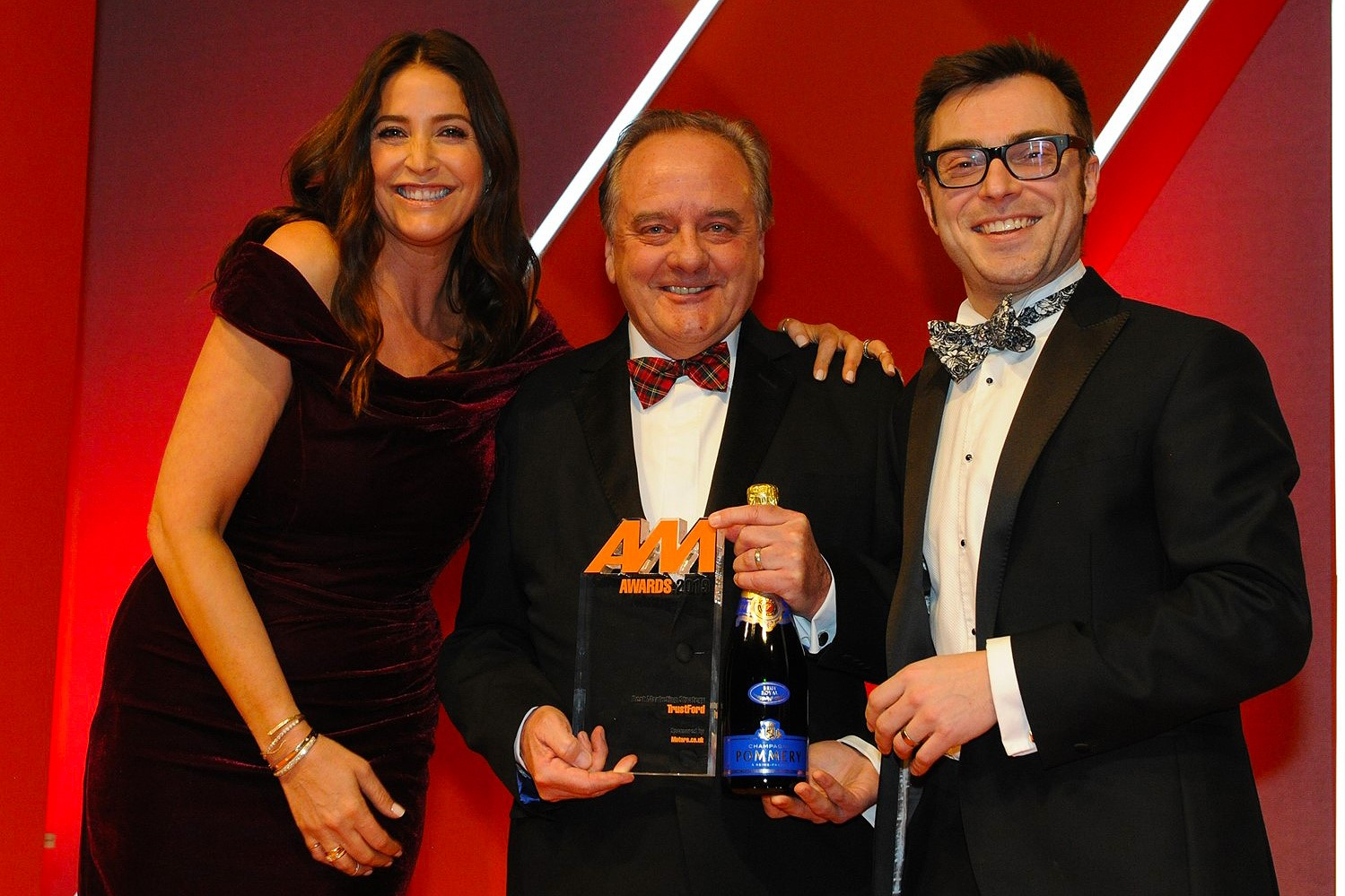 Stuart Foulds, chairman and chief executive,  TrustFord, accepts the award from Phill Jones,  managing director, Motors.co.uk, right, and host Lisa Snowdon left