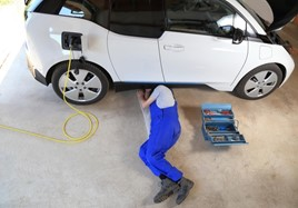 A car technician servicing a BMW i3 electric vehicle (EV)