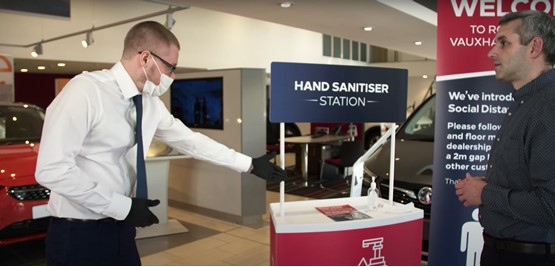 Vauxhall salesman with hand sanitiser for car buyer customer experience